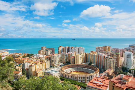 Beautiful iconic famous panoramic view of Malaga city center, a bullring, hotels, houses and Mediterrain sea seascape with cargo ships on sunny cloudy evening from Gibralfaro Castle, Andalusia, Spain.