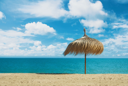 Beach umbrella made of palm leaves standing at the perfect dreamy paradise white yellow sandy bay beach by the blue sea and beautiful dramatic cloudy sky. A place for relax and vacations by the water.