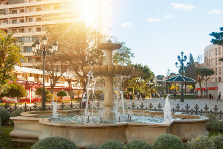 TORREMOLINOS, SPAIN - FEBRUARY 13, 2014: A beautiful stone fountain and lampposts, shops and hotels on the square Plaza de la Nogalera on warm summer sunset light, toned film effect background.