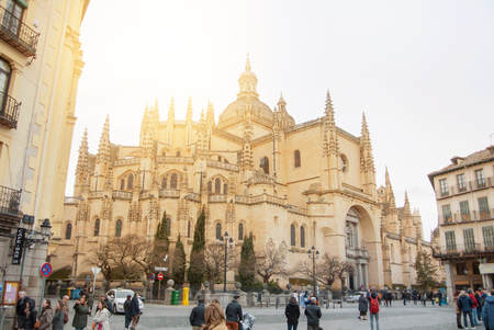 SEGOVIA, SPAIN - FEBRUARY 11, 2017: Medieval squere and Cathedral in the old historical center of Segovia, tourists walkind on sunny winter morning.