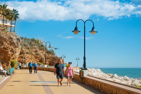 TORREMOLINOS, SPAIN - FEBRUARY 13, 2014: A promenade near Punta de Torremolinos, tourists, Mediterranean sea on sunny day. Concept of tourism vacation relax in Spain, elderly people moved to resorts. 新闻类图片