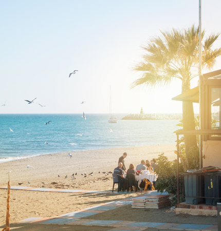 TORREMOLINOS, SPAIN - FEBRUARY 14, 2014: Tourists relaxing eating drinking at a beach bar along the promenade and palm trees with Maditerranean sea, beaches, lighthouse and seagulls at the backgrund. 新闻类图片