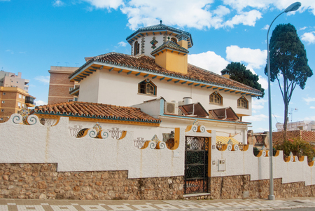 TORREMOLINOS, SPAIN - FEBRUARY 13, 2014: Beautiful decorated white typical mediterranean spanish house with high stone fence, a street, a concept of rent, buying a property, winter vacation in Spain. 新闻类图片