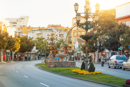 TORREMOLINOS, SPAIN - FEBRUARY 13, 2014: A typical road street with a fountain and a lamppost and flowers, orange trees, cafes, shops and cars on warm summer sunset light, toned film effect background 新闻类图片