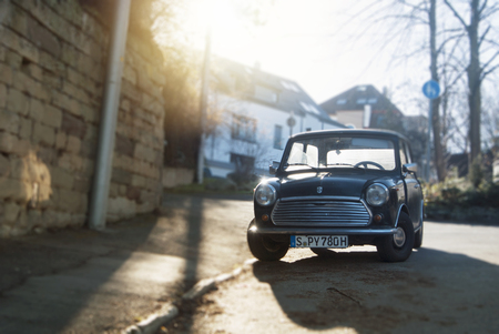 STUTTGART, GERMANY - DECEMBER 29, 2017: Old retro classic vintage oldtimer black mini copper car vehicle standing parked in the street near the stone wall.