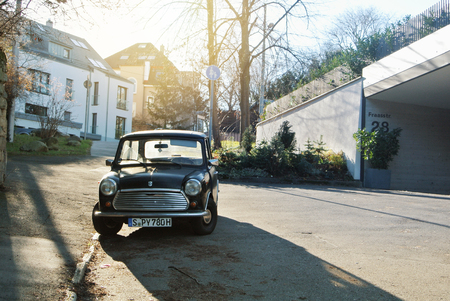 STUTTGART, GERMANY - DECEMBER 29, 2017: Old retro classic vintage oldtimer black mini copper car vehicle standing parked in the street near the stone wall in warm morning light.