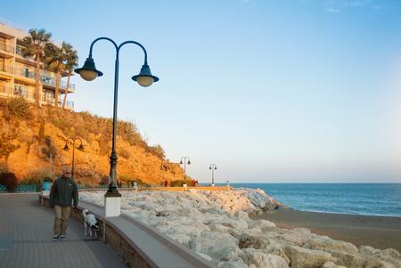 TORREMOLINOS, SPAIN - FEBRUARY 13, 2014: A promenade near Punta de Torremolinos, road, rocks, and Mediterranean sea on warm evening sunset sunlight, a man walking with a dog. Tourism vacation in Spain 新闻类图片