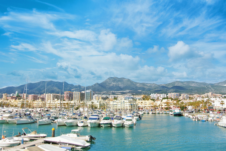Benalmadena Puerto Marina sport port, a view to piers with white modern luxury sport yachts, Mediterranean sea and mountains and cloudy sky at the background. Spain winter relax vacation concept. Stock Photo
