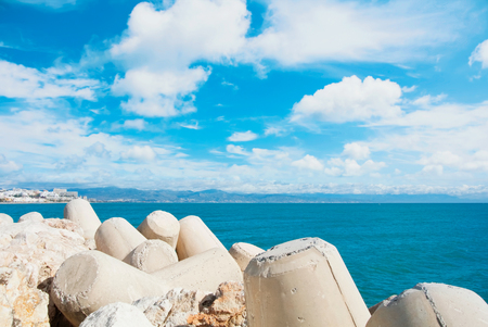 Beautiful panoramic aerial view over the big stones at the pier of Benalmadena port, a seashore with mountains, hotels, resorts and beaches at the background. Spain winter relax vacation concept.