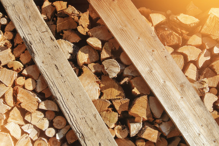 Natural rustic toned film effect hipster wooden background, dry chopped firewood spruce logs heaped in a wooden box for winter oven fare on the evening morning warm sunlight.