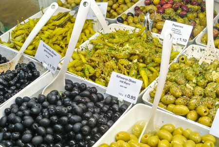Variety assortment diverse of fresh healthy tasty green and black olives in white plastic bowls for sale on open street city market in Stuttgart, Germany.