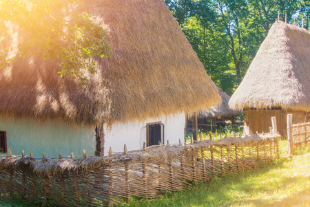 Old beautiful traditional romanian ukranian farm village house with white walls, roof covered with straw, wooden fence wickered by hand and a garden with wooden barn in warm sunlight on summer day. 免版税图像