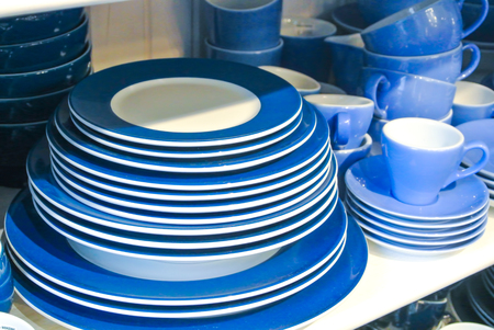 Bright blue and white dishes, plates and cups standing on white shelf. Concept of buying choosing new dishes for house home, interior indoor decoration o for gifts. Clean ordered dishes in store.