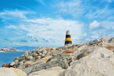 Little beautiful white, yellow and black lighthouse standing over the big stones at the pier of Benalmadena port, panoramic view to a seashore with hotels, resorts and beach. Spain winter vacation. 免版税图像