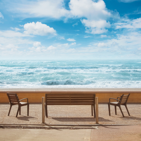 Beautiful panoramic view to benches standing in front of the sea shore coastline bay beach, blue transparent sea ocean waves and cloudy sky. A place for relax and vacations in a town by the sea water.