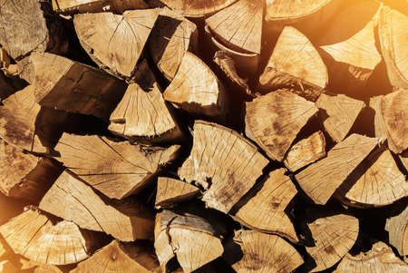 Close-up of pile of firewood toned texture background. Preparation of firewood for the winter for cooking, kindling of a fireplace. Stacks of firewood in the forest in warm morning evening sun light.