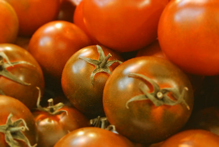 Close-up of red green fresh organic bio farm small round cherry tomatoes for sale, background with selected focus of vegetables at the street city roadside weekend market. Healthy local food.