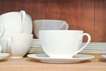 Bright white dishes, plates and cups standing on brown wooden shelf. Concept of buying choosing new dishes for house home, interior indoor decoration o for gifts. Clean ordered dishes in store.