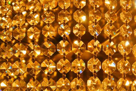 Bright golden gold yellow shiny abstract pattern, close up of details of a big beautiful luxury crystal chandelier, abstract indoor background with blur bokeh at the background.