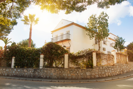Beautiful white typical mediterranean spanish house with high stone fence,  garden and trees on warm summer sunset light, toned film effect concept of rent, buying a property, winter vacation in Spain