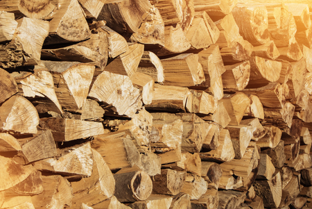 Pile of firewood toned texture background. Preparation of firewood for the winter for cooking, kindling of a fireplace. Stacks of firewood in the forest in the yard in warm morning evening sun light. 免版税图像