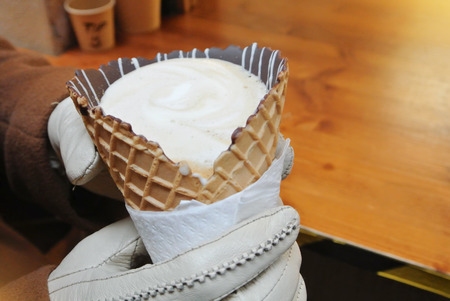 Closeup of woman girl hands in white gloves holding a cornettoccino, coffee with ice cream and milk in a waffle cone with chocolate. Hot drink in a street, lifestile urban love relationship and dating
