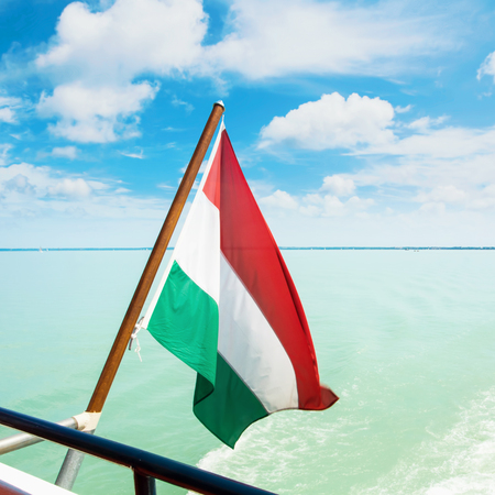 Hungarian flag flying fluttering waving in the wind at the forage of a cruise ship with beautiful dramatic cloudy sky and bright light blue water of Balaton lake at the background, Hungary.