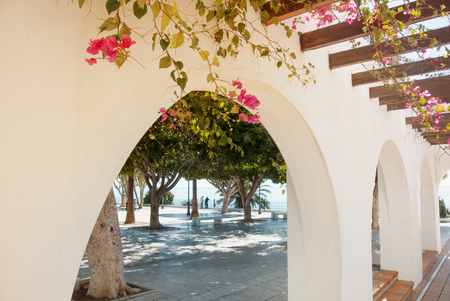 A view of bright white building with arch and pink violet bougainvillea and green trees in the street of small mediterranean town Torremolinos, Andalusia, Spain. A view point vith a view to a sea.