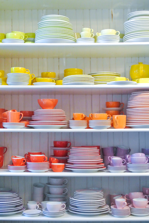 Bright colorful yellow red dishes, plates and cups standing on white shelf. Concept of buying choosing new dishes for house home, interior indoor decoration o for gifts. Clean ordered dishes in store.