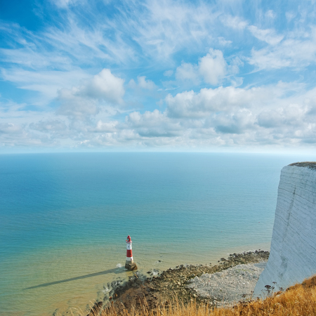 Aerial panoramic top view to famous red and white Beachy Head lighthouse and English Channel seascape with white chalk cliff of Beachy Head at the foreground and beautiful cloudy sky in the evening.