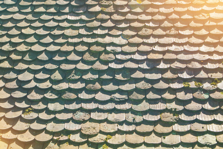 Background texture of old vintage tile roof of old european house in warm sunlight.