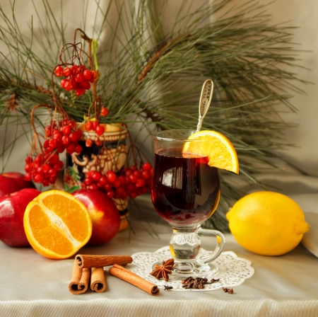 Glass of mulled wine, apples, oranges, cinnamon sticks and spices photo