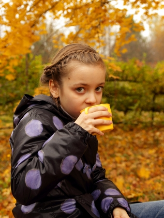 Pretty girl drinking hot tea from a cup on the background of the autumn landscape photo