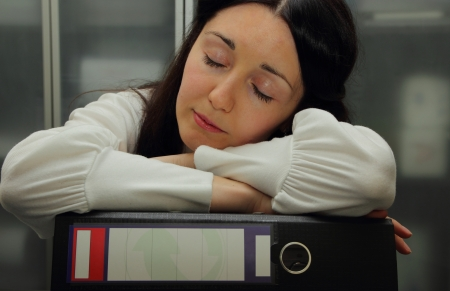Pretty girl asleep on folders with reports photo