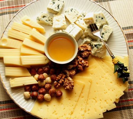 Cheese plate with several kinds of cheese, nuts and honey photo