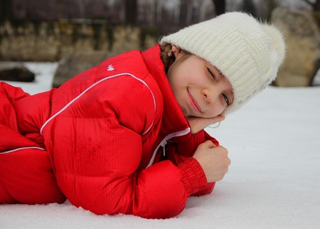squinting: Girl lying in the snow and squinting in the bright white light Stock Photo