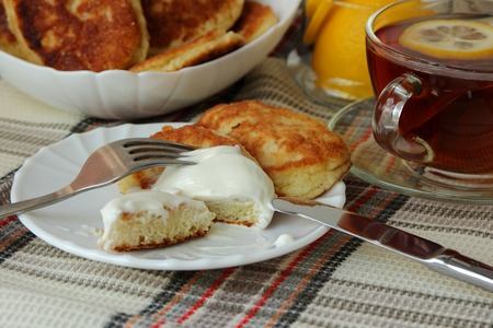Pancakes with sour cream and a cup of tea for breakfast photo