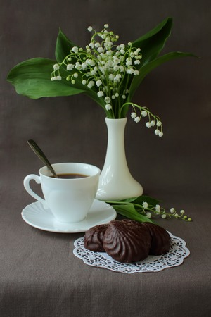 Bouquet of lilies of the valley, a cup of coffee and marshmallows  photo