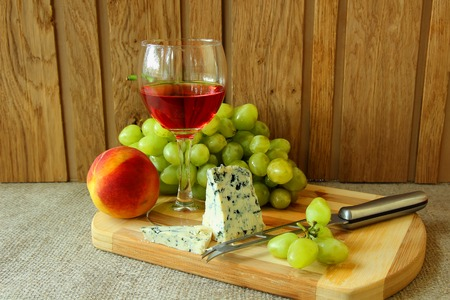 Still-life with a glass of rose wine, cheese and fruit  photo