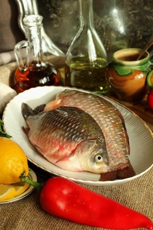 Fresh carp, herbs and vegetables photo