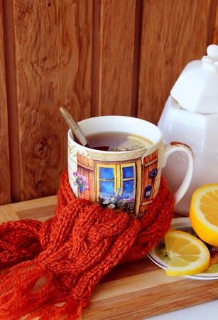 warming therapy: Warming cup of tea, tied with a scarf Stock Photo