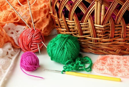 acrylic yarn: Several balls of colored yarn and a hook for tying lying near basket