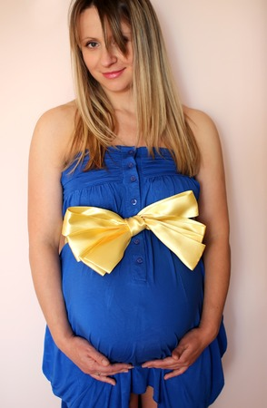 Pregnant woman in a dress with a bow
