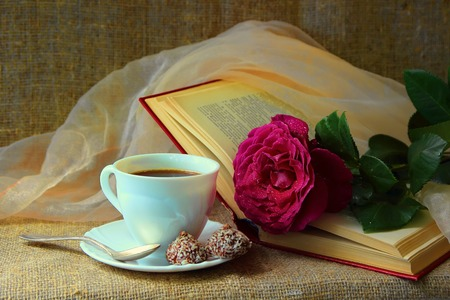 crimson colour: Rose, a cup of coffee and book