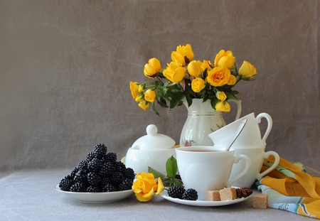 tea service: Still life with tea service and a bouquet of roses. Stock Photo