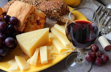 queso: Uvas, un plato de queso y un vaso de vino. Foto de archivo
