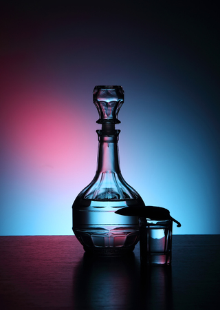 decanter: Decanter with vodka on a blue background. Stock Photo