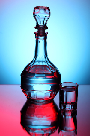 decanter: Decanter with vodka and a glass on a blue background.