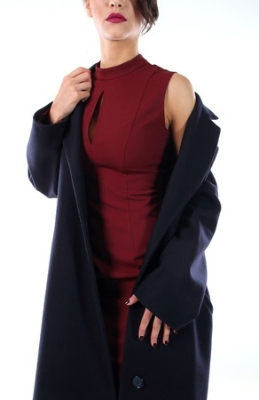 lapels: Young model in a dress claret color, takes off his coat of black Stock Photo