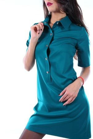 rigor: Young model in a a free cut dress of emerald color, standing in half a turn.